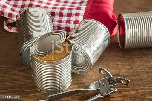 istock Old opener open to metallic can on the table in the kitchen. Canned food. Condensed milk. Healthy eating and lifestyle. 674441634