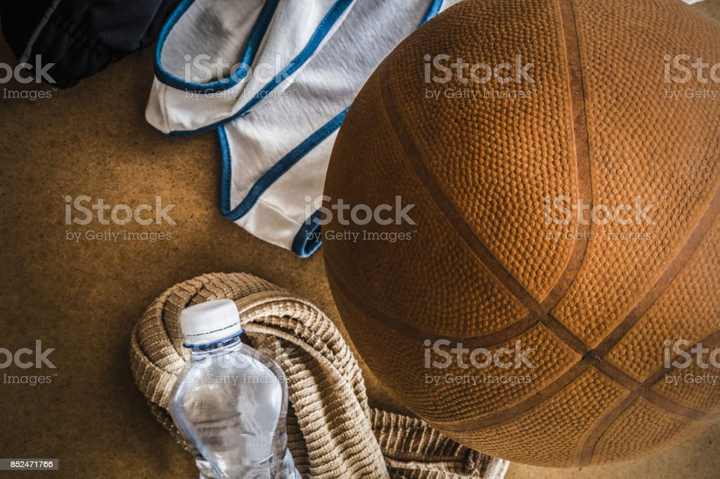 Old, orange basketball ball with accessories on the floor. Sport...