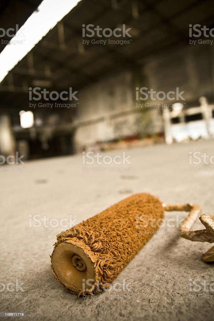 Old orange painting roller in a brownfield stock photo