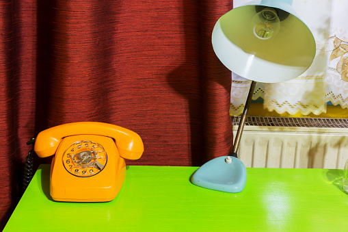 old orange scratched phone on green table