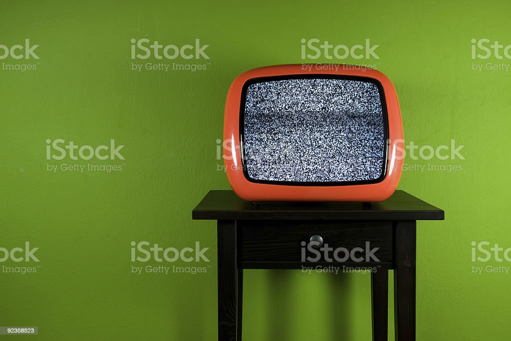 Old orange television with interruption in green room Old orange television with interruption in green room 1980 Stock Photo