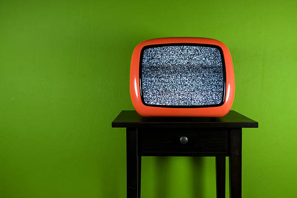 Old orange television with interruption in green room Old orange television with interruption in green room portable television stock pictures, royalty-free photos & images