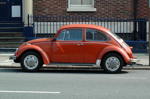 Liverpool, England - April 28, 2007:\nOld orange Volkswagen Beetle in the street