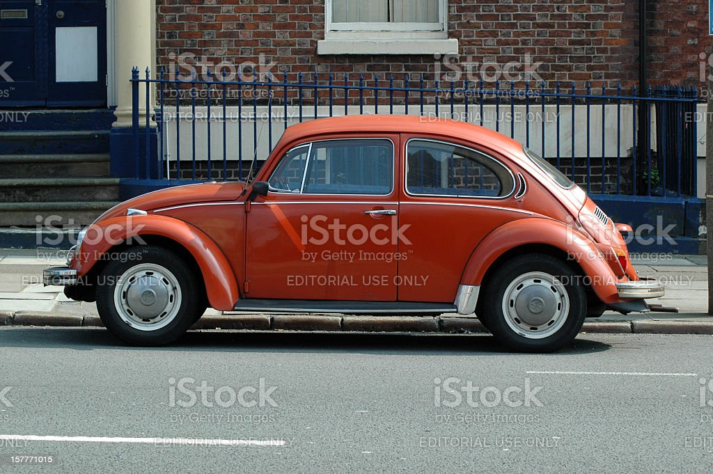 Old orange Volkswagen Beetle in the street stock photo