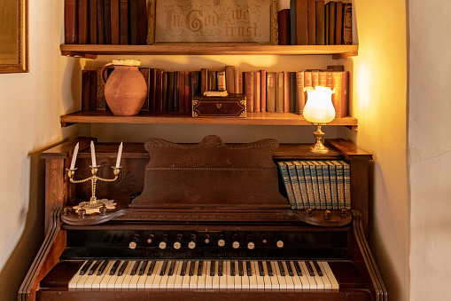 Old organ with antique books in an alcove with a lamp