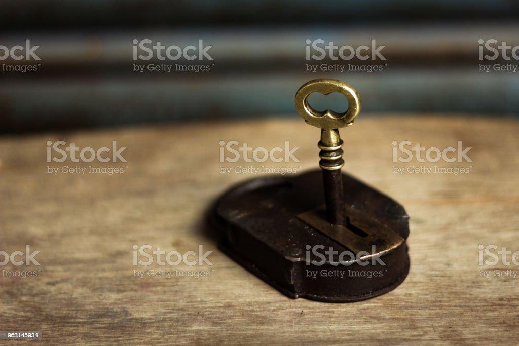 Gamla original gyllene nyckel släpper en brun metall hänglås - Royaltyfri Antik Bildbanksbilder