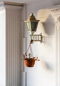 Old ornate lamp with hanging flower pot and white wall background.