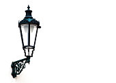 Old ornate street lamp against white walls background with copy space, full frame horizontal composition