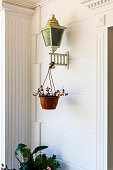 Old ornate street lamp with hanging flower pot and white wall background.