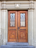 Old ornated wooden double door with stone doorframe