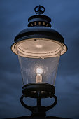 Old black and vintage design outdoor lamp, glowing in the dark with a dark and cloudy overcast sky as background