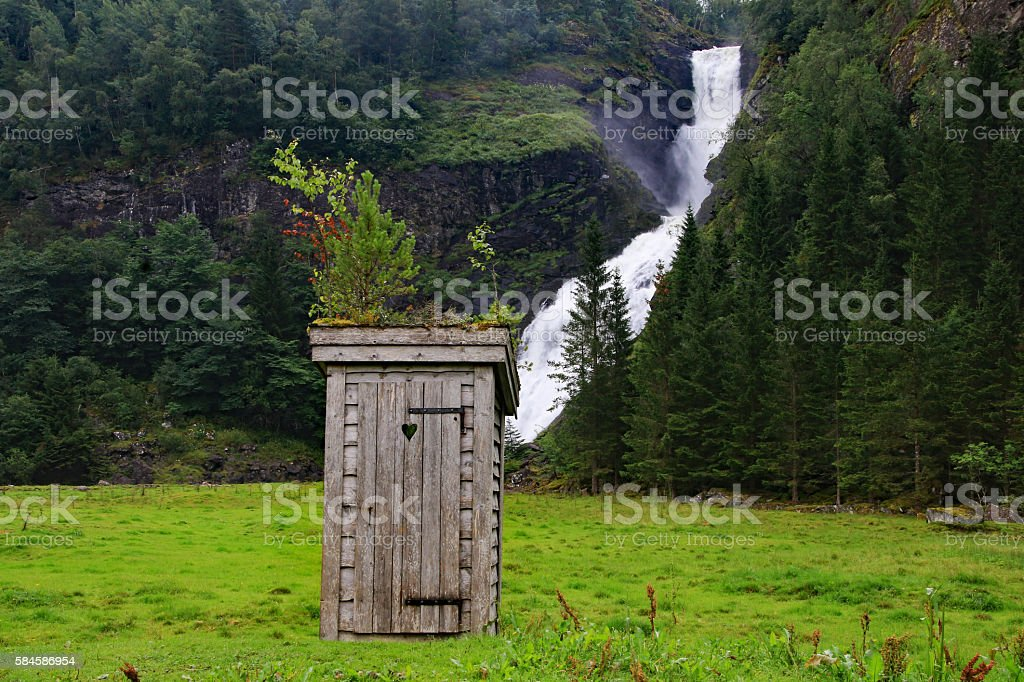 Old outdoor privy in front of waterfall stock photo