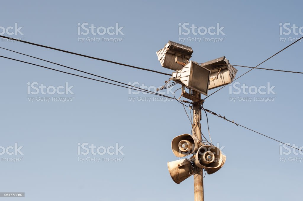 Old outdoor public loudspeakers, megaphones and reflectors on metal pole with black electric cables royalty-free stock photo