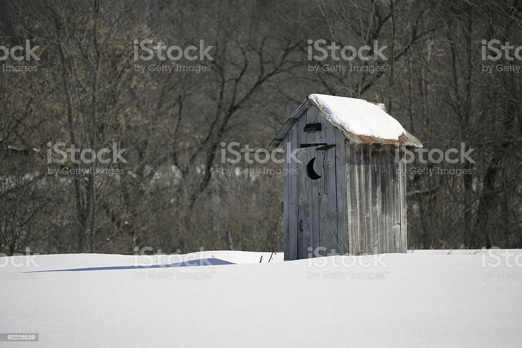 Old Outhouse in Snow Covered Field stock photo