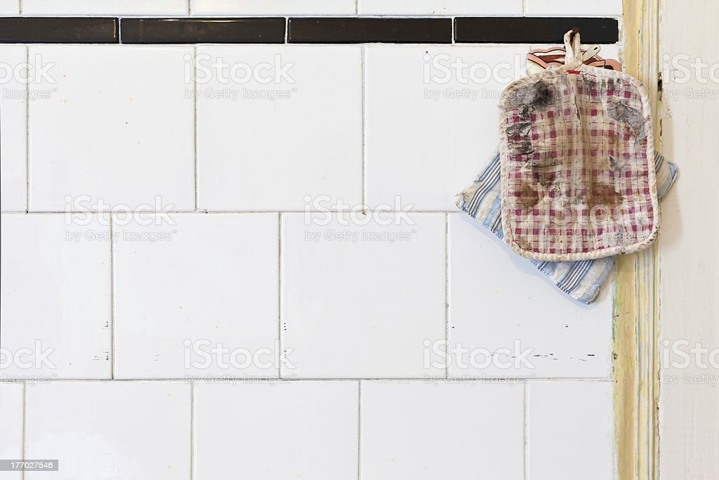 Old Oven Mitts on a dirty kitchen wall royalty-free stock photo