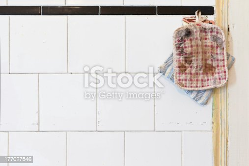839034546 istock photo Old Oven Mitts on a dirty kitchen wall 177027546