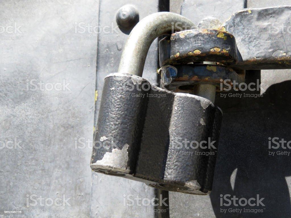 Old padlock with peeling paint on metal door royalty-free stock photo