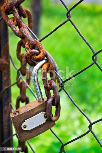 Old padlock with rusting chain on the wire netting as background over green earth