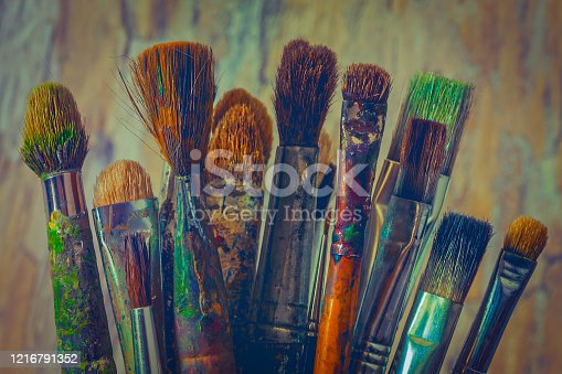 Old brushes for painting,smeared with colored paint, are in the artist's  studio