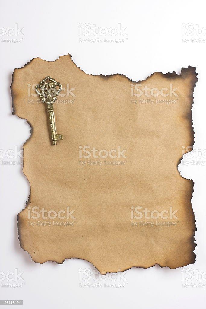 Vecchia carta bruciata sui bordi con una chiave d'oro. foto stock royalty-free