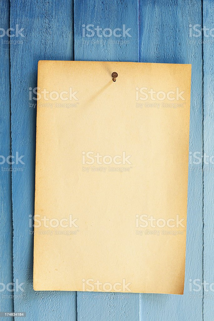 Old paper nailed to a blue weathered wooden board. royalty-free stock photo