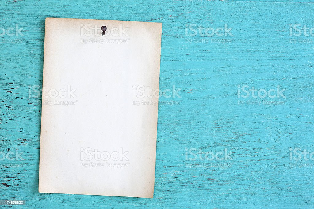 Old paper nailed to a turquoise weathered wooden board. royalty-free stock photo
