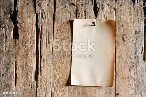 Old paper nailed to an old weathered wooden board with a rusty nail.