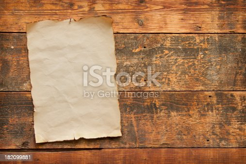 close up of an old worn blank piece of paper with burnt and torn edges, nailed to an old weathered plank door