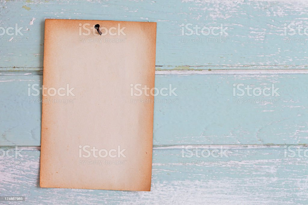 Old paper nailed to weathered wooden panelling. royalty-free stock photo