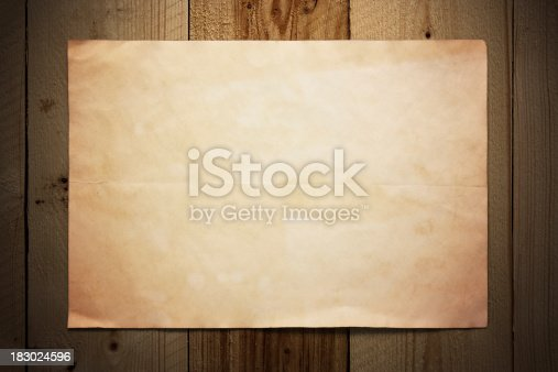 istock Old paper on wooden wall 183024596