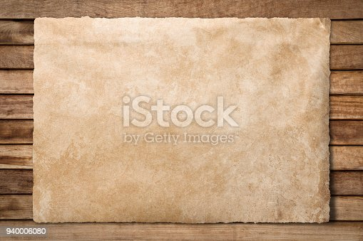 istock Old paper sheet at wooden background 940006080