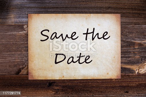 Old Grungy Paper With English Text Save The Date. Wooden Background