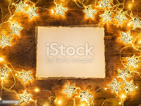 636659848 istock photo Old paper with garland on wooden background. 636658386