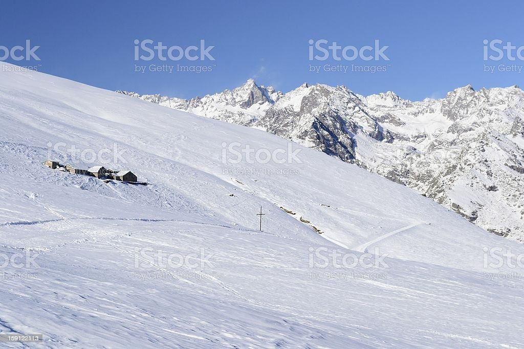 Old pasture huts in scenic winter background royalty-free stock photo