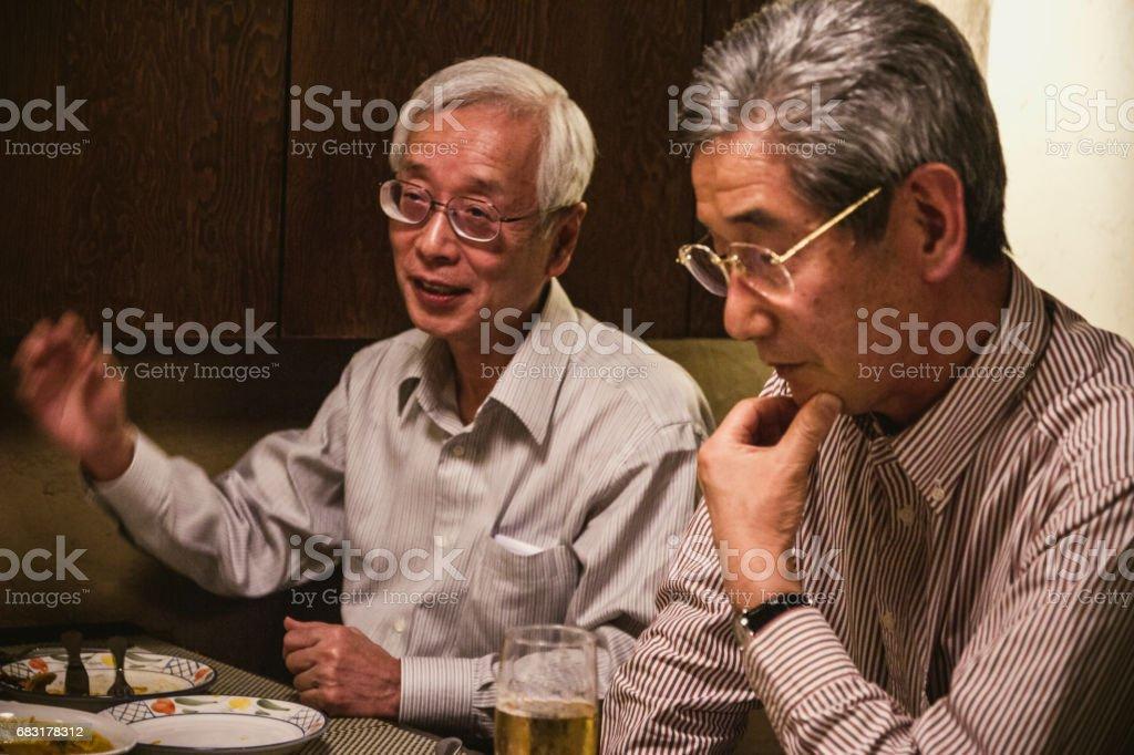 저녁 식사 파티에서 주장 하는 노인 royalty-free 스톡 사진