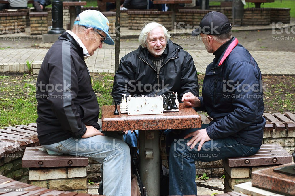old people, friends, playing a game of chess outdoor. stock photo