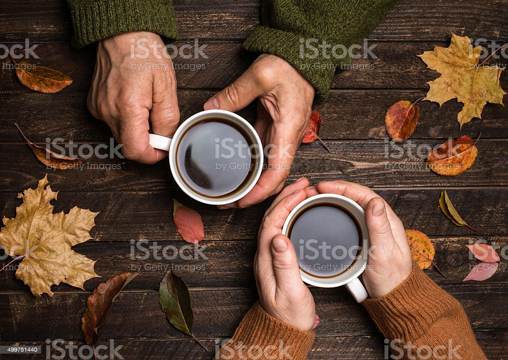Old people hands. Closeup. Senior hands holding coffee cups. stock photo