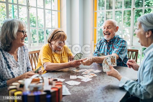 Group of senior friends playing cards in the nursing home and having fun