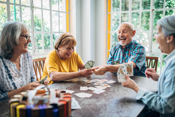 Old people having fun playing cards in nursing home stock photo