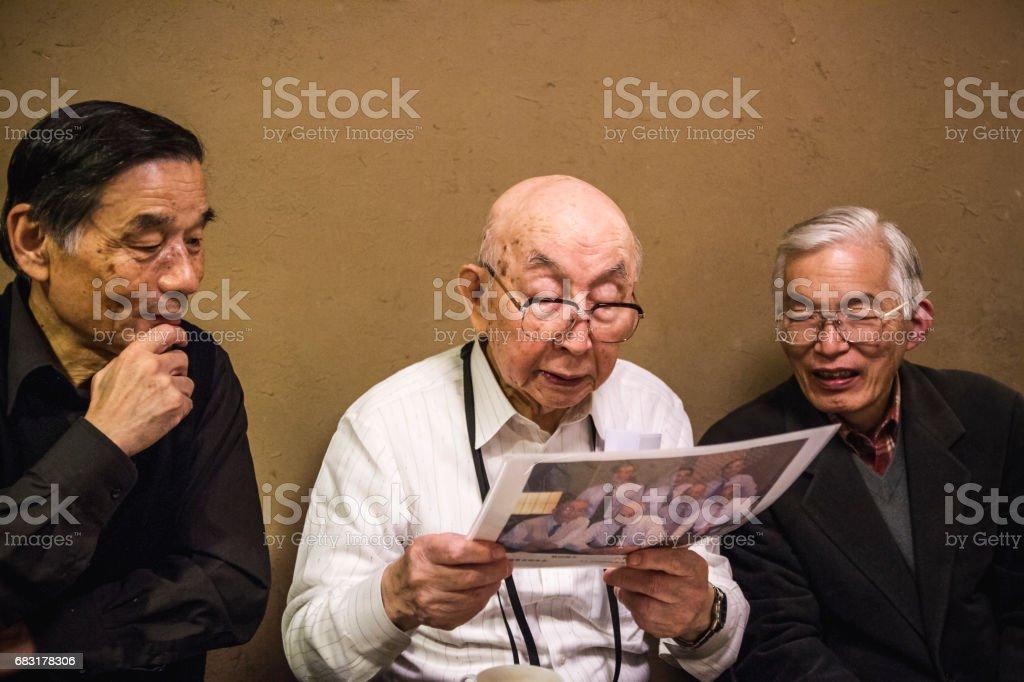 오래 된 사람들이 함께 방에 있는 그림을 보고. royalty-free 스톡 사진