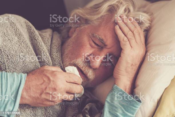 Old people senior man with winter seasonal illness fever cold problems drinking a pharmacy medicine or hot tea to go healthy - concept of mature retired with disease Old people senior man with winter seasonal illness fever cold problems drinking a pharmacy medicine or hot tea to go healthy - concept of mature retired with disease 70-79 Years Stock Photo