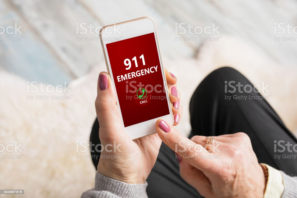 Old person dialing emergency number 911 on phone stock photo