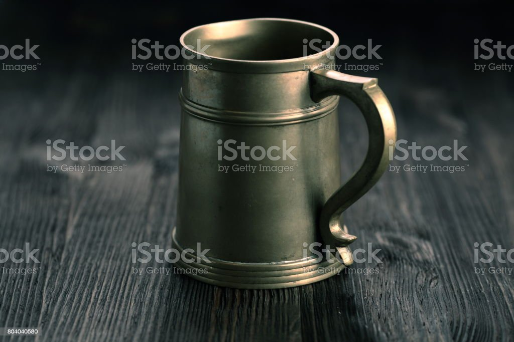 Old Pewter Mug on a wooden table stock photo