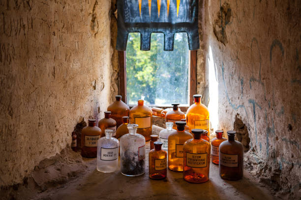 Old pharmacy bottles with latin names. Room of medieval doctor in castle. stock photo