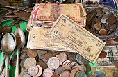 Very old Philippine bank notes and coins mixed with antique spoons on a table in a wet market in the city of Iloilo, Philippines