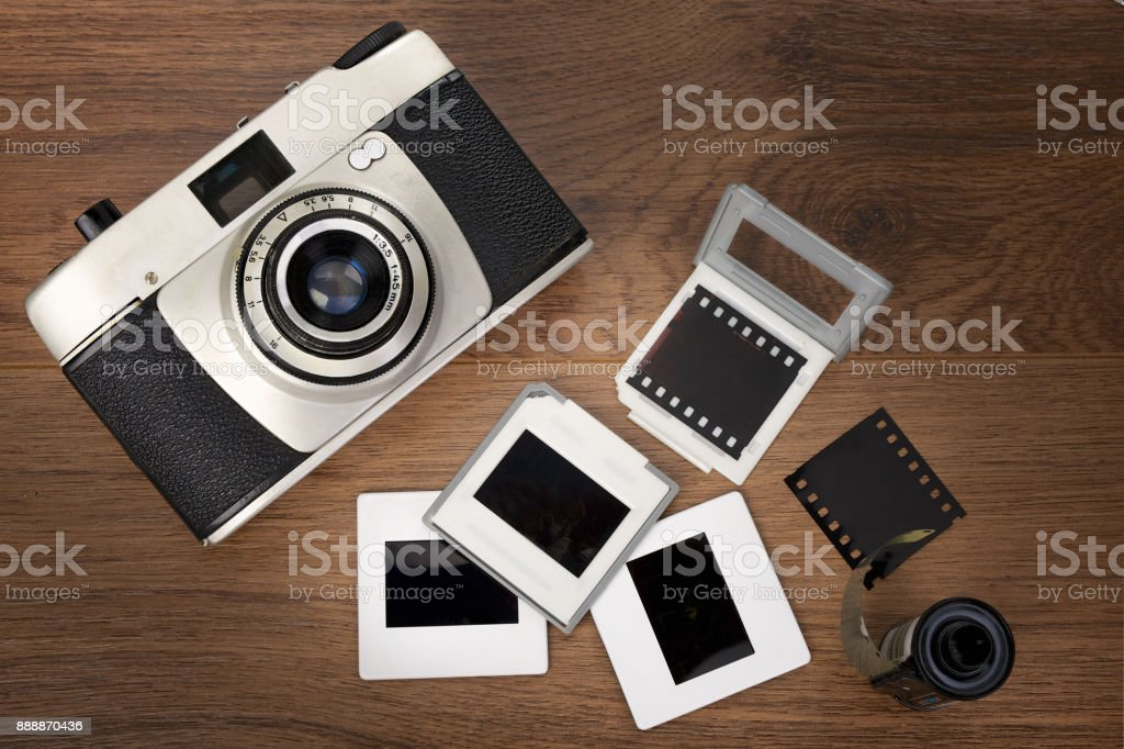 Old photo camera and mounted film slides on wooden background stock photo