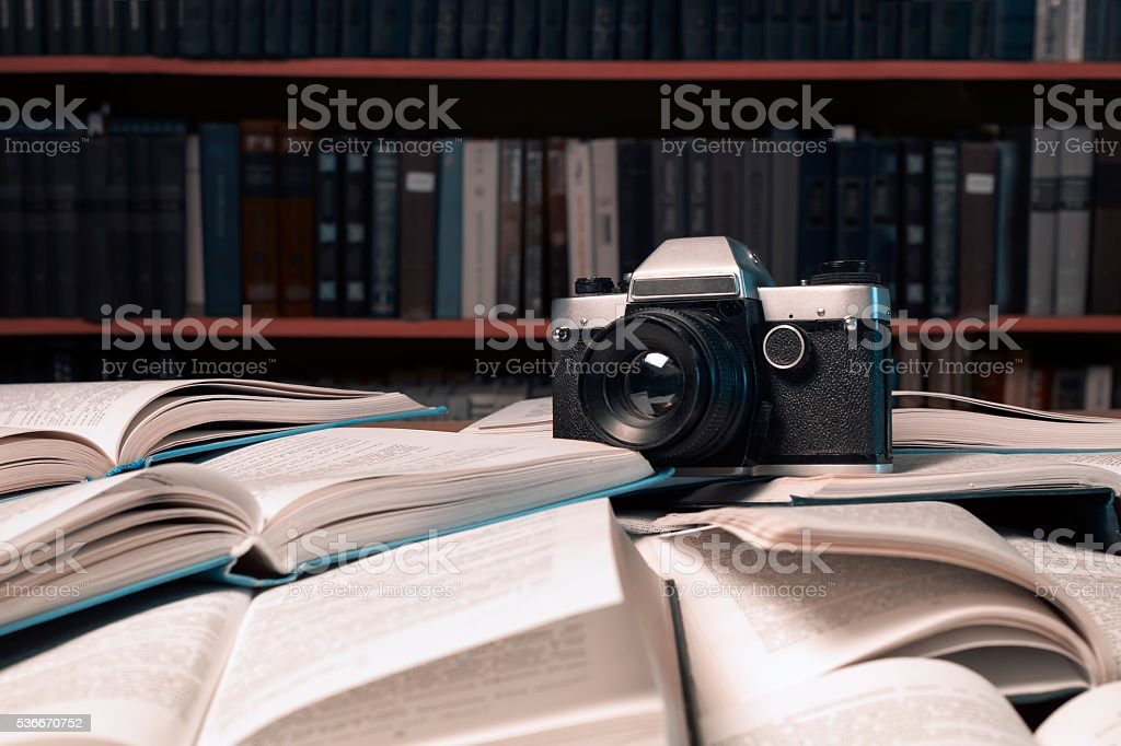 Old photo camera  is on many  open books stock photo