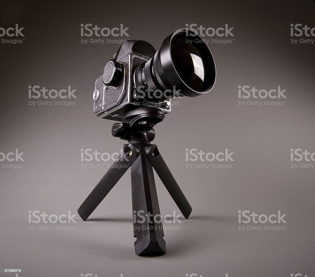 Old photo camera with tripod on grey in Hi-Res royalty-free stock photo