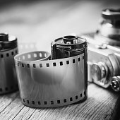 Old photo film cassette and retro camera on background.