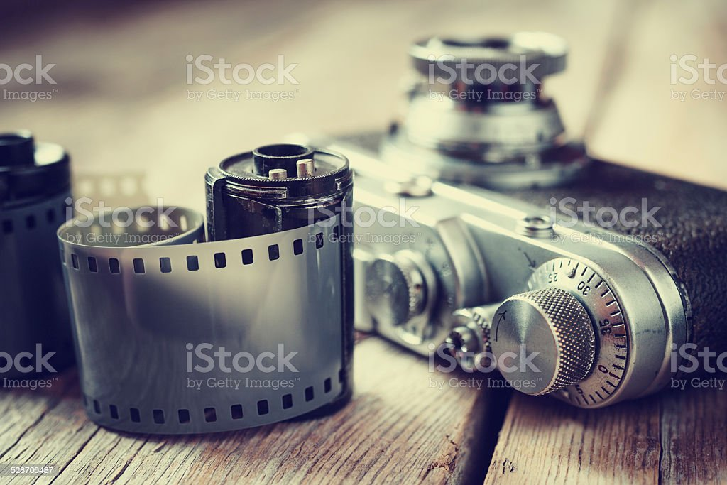 Old photo film rolls, cassette and retro camera, selective focus